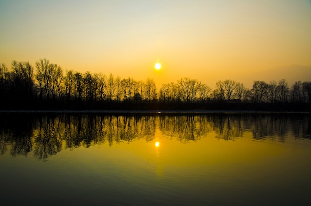 Beau coucher de soleil sur le lac avec des silhouettes d'arbres reflétées dans l'eau