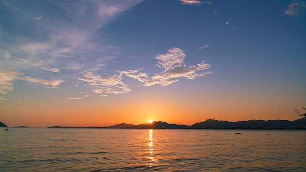 Beau coucher de soleil léger sur le ciel dramatique de la mer.
