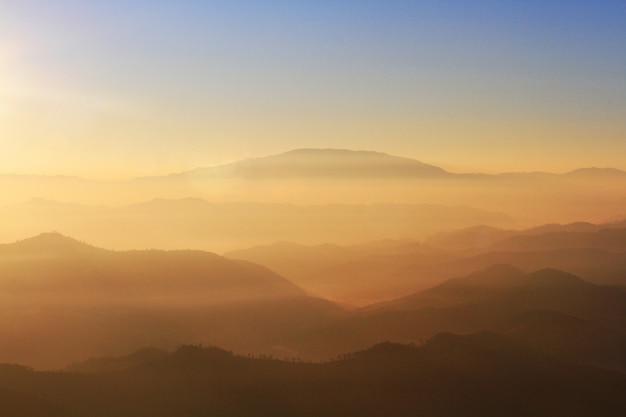 Beau coucher de soleil et lever de soleil sur ciel et crépuscule doré avec brouillard et brouillard dans la vallée de la couche de montagne