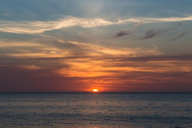 Beau coucher de soleil sur la mer avec des nuages violets