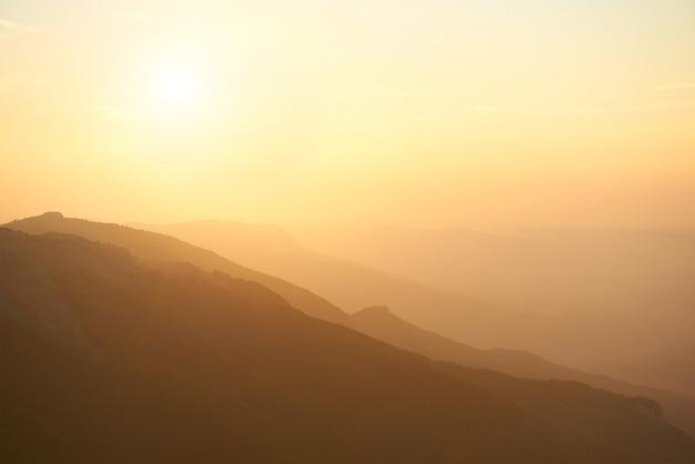 Beau coucher de soleil sur les montagnes. paysage dramatique avec soleil et ciel orange