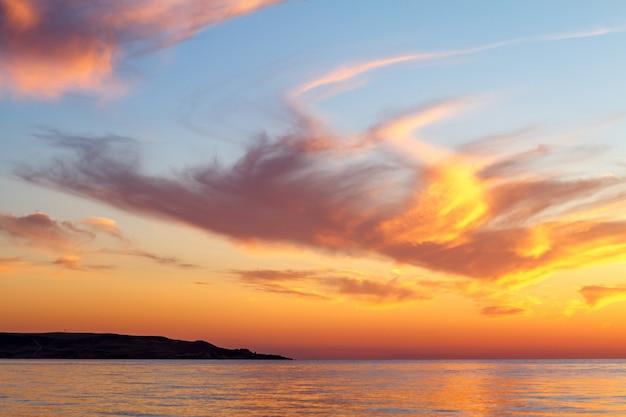 Beau coucher de soleil nuages dans le ciel au-dessus de la mer, couleurs vives du coucher du soleil.