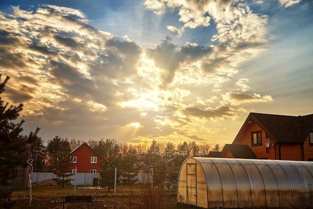 Beau coucher de soleil et nuages avec rayons de soleil en soirée sur petite maison de village.