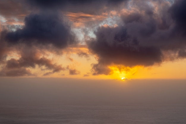 Beau coucher de soleil sur l'océan avec du brouillard à l'horizon et des nuages sombres dans le ciel