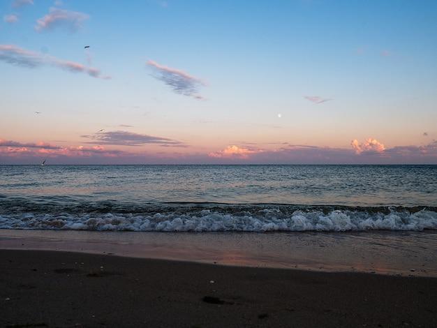 Beau coucher de soleil sur une plage. coucher de soleil d'été et vagues de la mer.