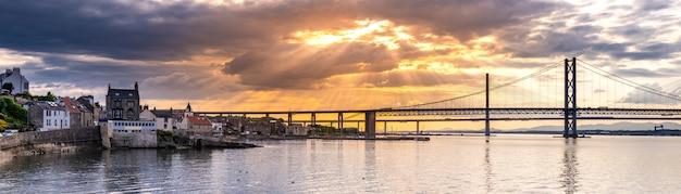 Beau coucher de soleil sur le pont routier forth et le pont de croisement de queensferry à edimbourg