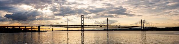 Beau coucher de soleil sur le pont routier forth et le pont de croisement de queensferry