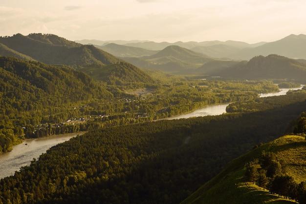 Beau coucher de soleil sur la rivière dans l'altaï dans la campagne vallonnée