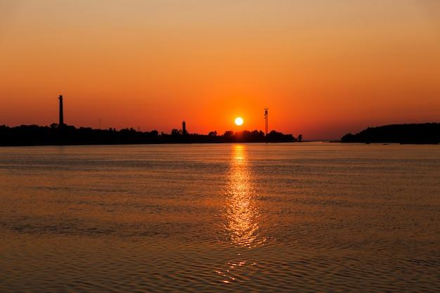 Beau coucher de soleil sur la rivière. silhouette de la ville industrielle .. soleil orange dans le ciel