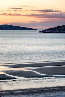 Beau coucher de soleil rose sur la mer. magnifique nature nordique. verticale.