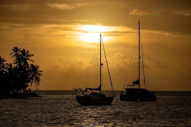 Beau coucher de soleil avec silhouette de deux voiliers et palmiers sur l'île, liberté de voyage et avènement...