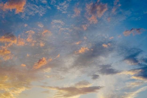 Beau coucher de soleil avec le soleil des tons oranges derrière les montagnes et le ciel bleu profond