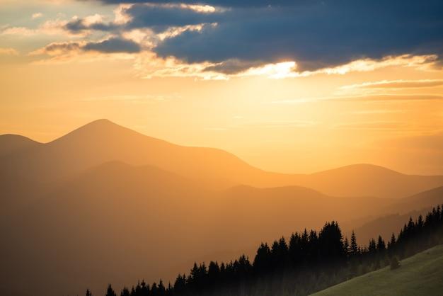 Beau coucher de soleil spectaculaire dans les montagnes. paysage avec soleil qui brille à travers les nuages orange