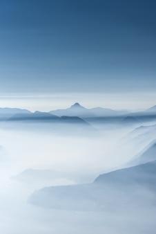 Beau coup de hautes collines blanches et de montagnes couvertes de brouillard