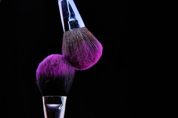 Beau coup de pinceau de maquillage isolé sur fond noir