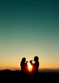 Beau coup de silhouettes d'un couple buvant du vin au coucher du soleil