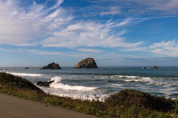 Beau coup de vagues de mousse frappant un bord de mer rocheux