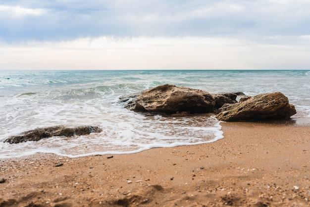 Beau coup de vagues sur une plage de sable