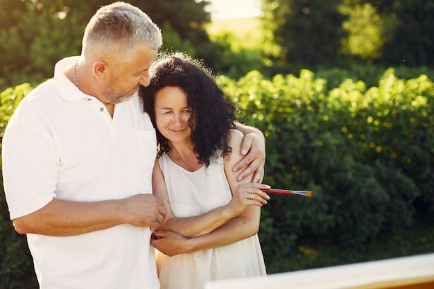 Beau couple adulte dessinant dans un champ d'été