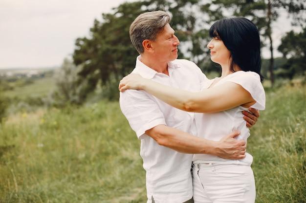 Beau couple adulte passe du temps dans un champ d'été
