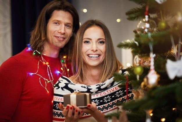Beau couple adulte avec présent sur l'arbre de noël