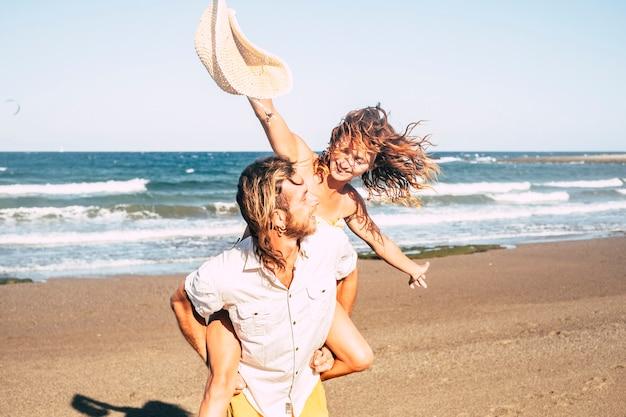 Beau couple d'adultes s'amusant ensemble à la plage sur le sable - homme marchant avec sa femme ou sa petite amie sur lui - il la tient - femme aux bras ouverts soit heureuse