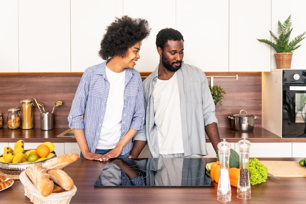 Beau couple afro-américain cuisinant à la maison - beau et joyeux couple noir préparant le dîner ensemble dans la cuisine