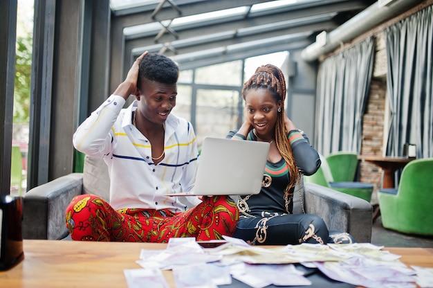 Beau couple afro-américain élégant assis au bureau avec ordinateur portable et argent. ils ont des visages choqués.
