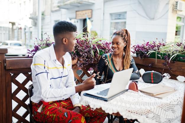 Beau couple afro-américain élégant assis au café en plein air avec ordinateur portable.