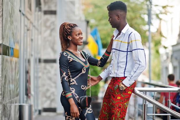 Beau couple afro-américain élégant posé dans la rue ensemble dans l'amour.