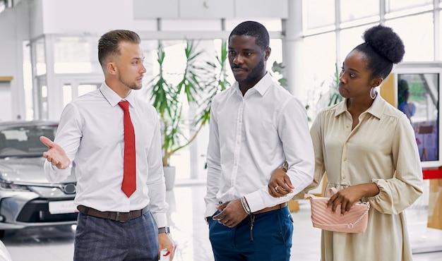 Beau couple afro noir écoute attentivement le consultant en concession
