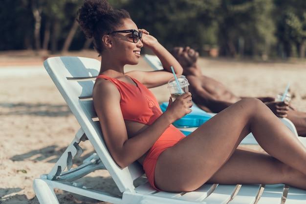 Beau couple afro se repose sur la plage de sandy river