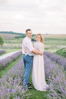 Beau couple d'âge moyen embrassant au champ de lavande. concept de portrait d'amour, de personnes, d'émotions et de style de vie à l'extérieur