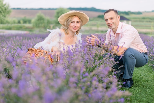 Beau couple d'âge moyen romantique heureux assis dans un champ de lavande et regardant la caméra