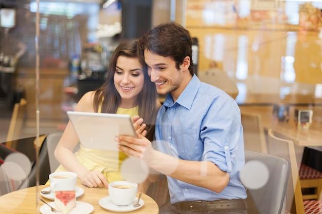 Beau couple à l'aide de tablette numérique au café