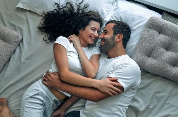 Beau couple aimant s'embrasser dans son lit