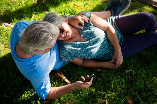 Beau couple d'aînés mariés allongés sur l'herbe regardant le même téléphone ou appareil dans le parc