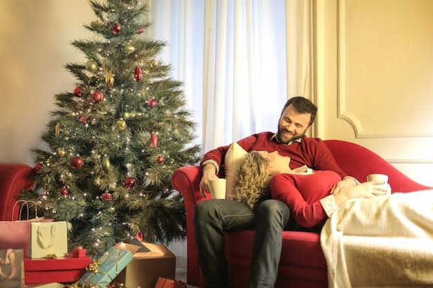 Beau couple allongé sur le canapé, célébrant noël ensemble