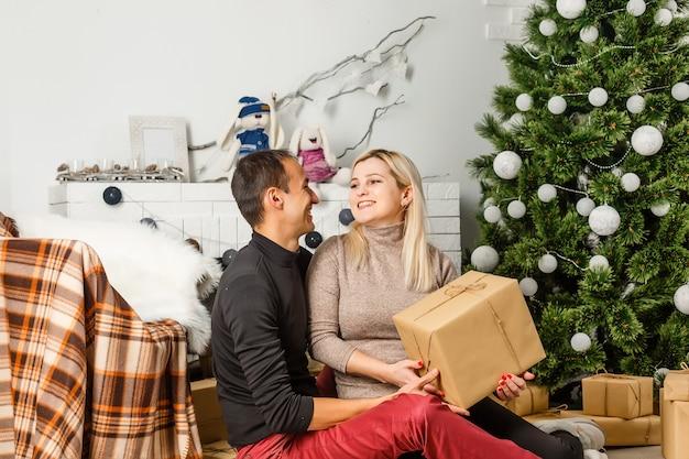 Beau couple amoureux assis sur un tapis devant la cheminée. femme et homme fêtant noël