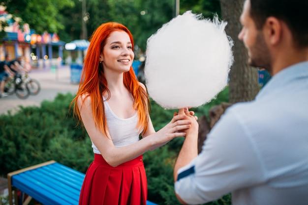 Beau couple amoureux avec barbe à papa dans le parc d'été, réunion romantique à l'extérieur. jolie femme et jeune homme s'amuse ensemble