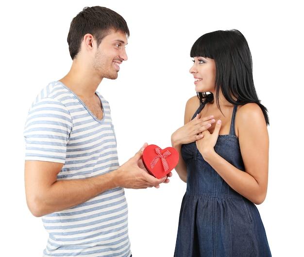 Beau couple d'amoureux avec cadeau isolé sur une surface blanche