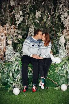 Beau couple amoureux dans des pulls confortables avec impression de noël s'embrassant ensemble