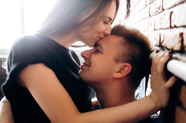 Le beau couple amoureux embrassant et assis sur le lit
