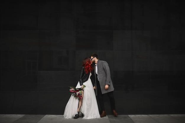 Beau couple d'amoureux embrasse à l'extérieur pendant la séance photo de mariage. slim jeune femme aux cheveux rouges dans une veste en cuir et une robe de mariée et un bel homme barbu en manteau.
