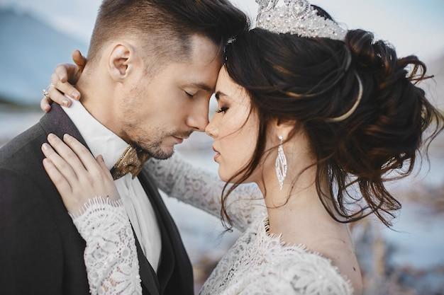 Beau couple d'amoureux étreignant, une jeune femme avec une coiffure de mariage et des bijoux de luxe et bel homme brutal en costume et noeud papillon