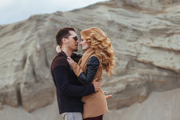 Beau couple amoureux le jour de la saint-valentin. heureux jeune couple marchant sur les montagnes de sable sur une journée nuageuse