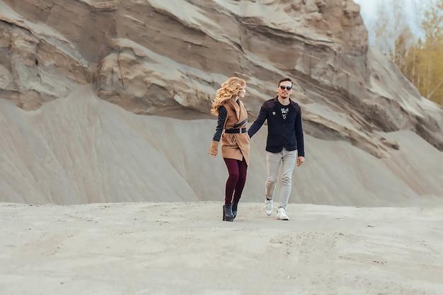 Beau couple amoureux le jour de la saint-valentin. heureux jeune couple marchant sur les montagnes de sable par temps nuageux