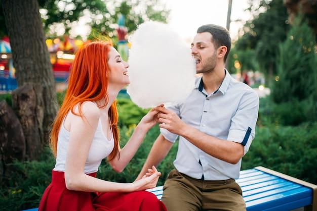 Beau couple amoureux mange de la barbe à papa sur un banc dans le parc d'été, réunion romantique à l'extérieur. jolie femme et jeune homme s'amuse ensemble