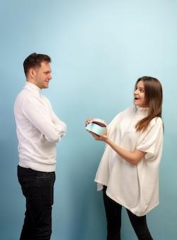 Beau couple amoureux sur mur bleu studio