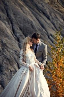 Beau couple amoureux sur un paysage fabuleux, mariage dans la nature, baiser d'amour et câlin